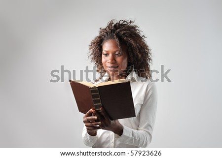 A black woman is reading a book - stock photo