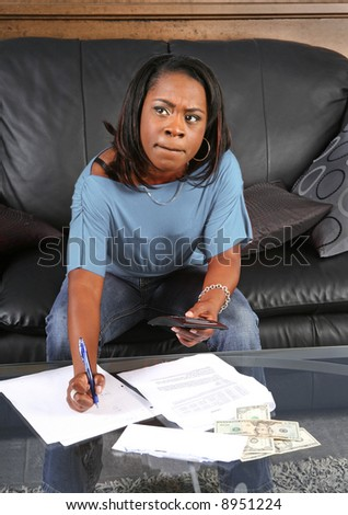 a black woman with a calculator very concerned about big bills - stock photo