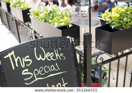 A blackboard in front of a cafe in Chicago, Illinois mentioning the special menu of the week. On the background, people are seen having their food in the restaurant. - stock photo