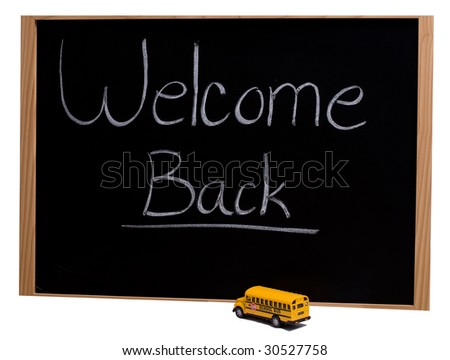 """A blackboard with the words """"welcome back"""" and a toy school bus parked in front of it - stock photo"""