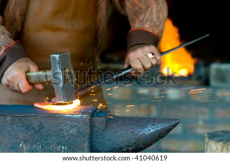A blacksmith forging a horseshoe with a hammer onto anvil at the foreground. A forging furnace with fire at the background. - stock photo