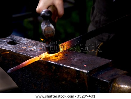 A blacksmith hammering a hot metal rod to shape it. - stock photo