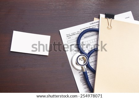 A blank, a medical record form with a  stethoscope on a wooden desk - stock photo