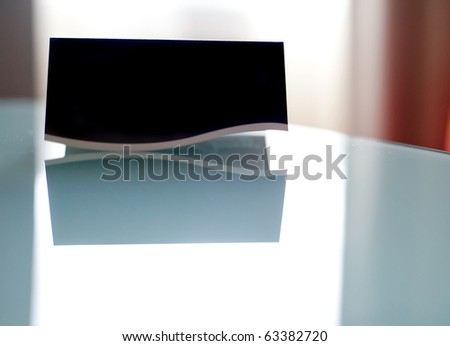 A blank black business card on a reflective surface. - stock photo