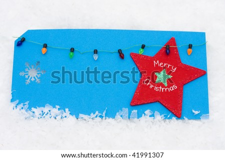 A blank blue card on a snow background with Christmas lights, merry christmas