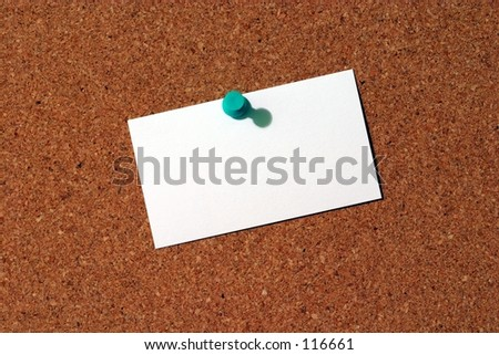 A blank business card tacked to a corkboard. - stock photo