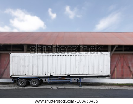 A blank cargo freight container on a truck trailer in front of a vintage timber warehouse.