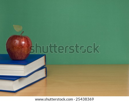 A blank chalkboard with an apple over books.