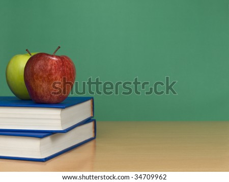 A blank chalkboard with two apples over books. - stock photo