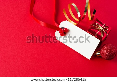 A blank Christmas gift tag, with red ribbon and artificial holly berries, on matte red background with shiny small gift box, glittery bauble, and gold foil spiral.  Copy space on tag and to it's left. - stock photo