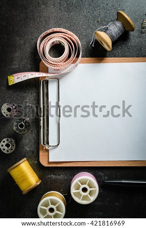 A blank clipboard and set of manual tools on grunge dark background