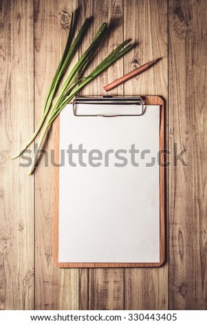 A blank clipboard on wooden background for copy-space. Top view - stock photo