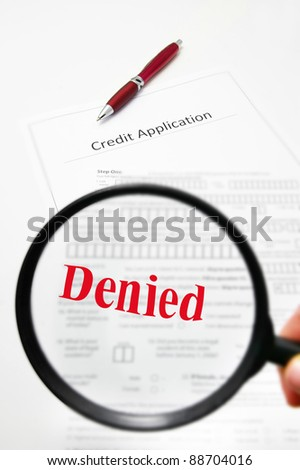 a blank credit application and magnifying glass with Denied text - stock photo