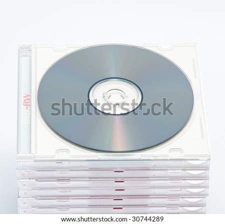 a blank dvd or cd with stack of empty cd cases on background - stock photo