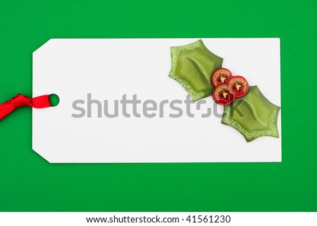 A blank gift tag with holly on a green background