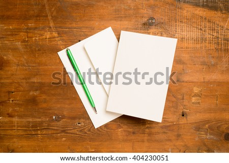 A blank greeting or invitation card with envelope and green writing pen on a wooden surface for copy space. - stock photo