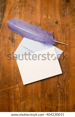 A blank greeting or invitation card with envelope and purple feather on a wooden surface for copy space. - stock photo