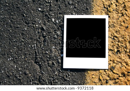 A blank instant photo lying in the street. - stock photo