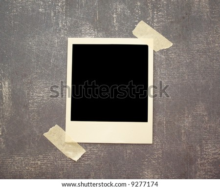 A blank instant photo taped to a grungy background. - stock photo