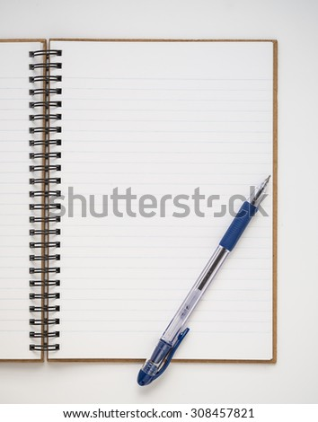 A blank lined notebook with blue pen on white background - stock photo