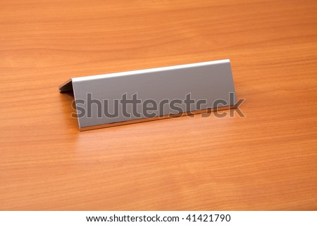A blank metal name plate on a desk.  Ready for text to be added.