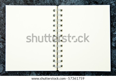 A blank note book on a dark background.