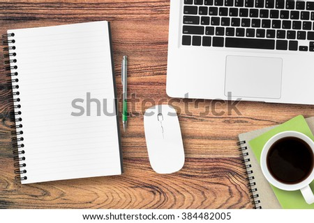 A blank notebook page and pen on wood office table with laptop and a cup of coffee. Top view. Digital life style concept. - stock photo