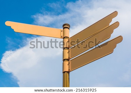 A Blank Orange / Brown Colored Road Sign, with Background of Blue Sky and White Cloud. - stock photo