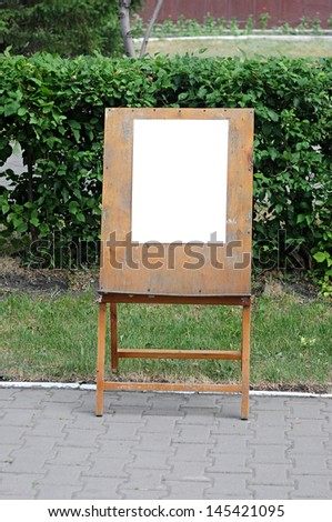 a blank painter easel over green background - stock photo