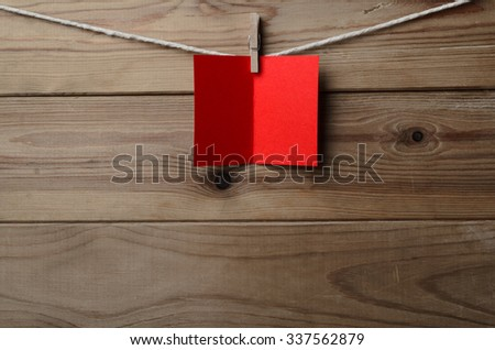 A blank, red greetings or Christmas card, pegged to string against old wood planked background.  Copy space on card and below. - stock photo