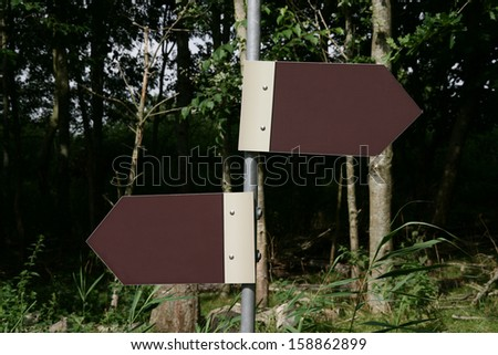 A blank roadsign pointing in two directions. With space for own text. - stock photo