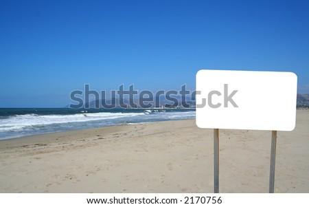 A blank sign on the beach. - stock photo