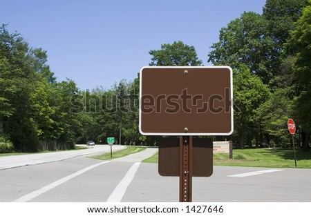 A blank sign posted along roadway in a park.  Add your own message