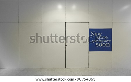 A blank timber panel wall with a sign indicating a new store is opening here soon, inside a building complex. - stock photo