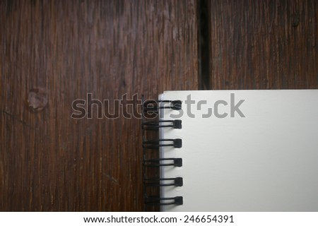 a blank white notebook on wooden table - stock photo