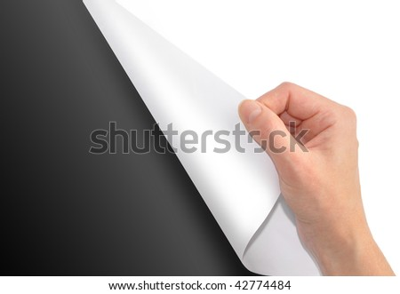 A blank white piece of paper is being turned by a hand and the background is black. Add your text to the black side of the paper. - stock photo