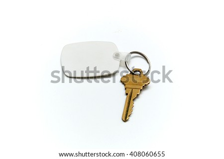 A blank white rubber key fob on keyring with a single brass key laying on white surface. Copy space on fob and white. Not Isolated.