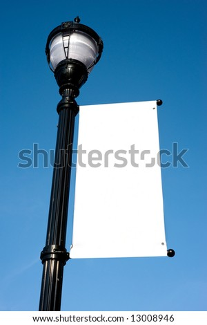 A blank white sign on a lamp-post in front of a blue sky, add your own copy or graphic, copy space.  Includes clipping path for sign area - stock photo