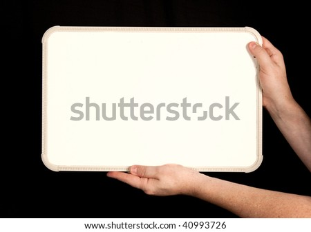 A blank whiteboard in a man's hands isolated against a black background.