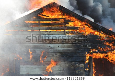 A blazing fire burns through the roof rafters of an old farm home. - stock photo