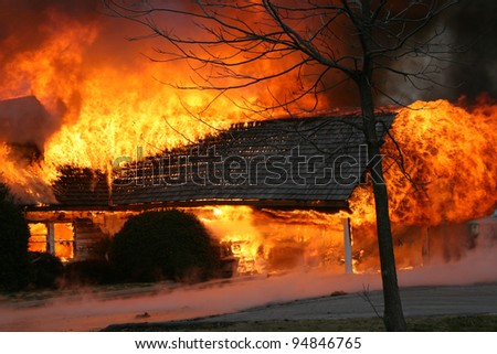 A blazing house fire engulfs a porch.  Fire is one of the most destructive forces of nature, killing thousands each year and leaving nothing but ashes in it's wake - stock photo