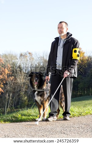 A blind man goes for a walk with his guide dog - stock photo