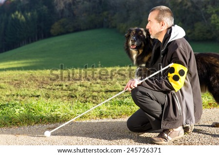 A blind man kneels next to his attentive guide dog - stock photo