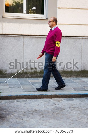 A blind man walks with a cane on a street