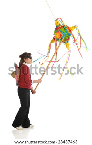 A blindfolded elementary girl hitting a traditional Mexican pinata with a stick.  Isolated on white. - stock photo