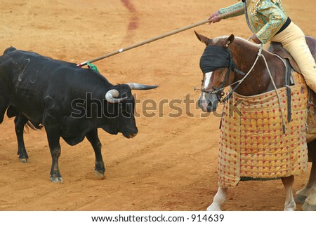 a blindfolded horse and a bull during corrida in sevilla