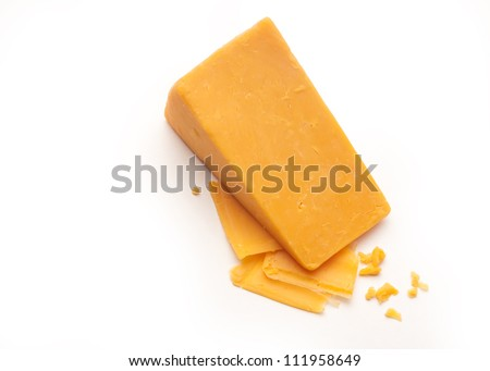 A block cheddar cheese on top of some cheese shavings and crumbs on a white isolated background. - stock photo