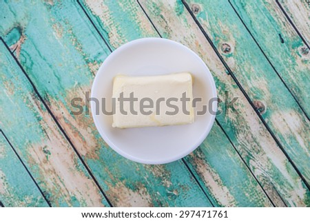 A block of butter in white bowl over rustic wooden background - stock photo