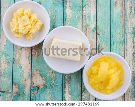 A block of butter, margarine and ghee in white bowls over rustic wooden background - stock photo