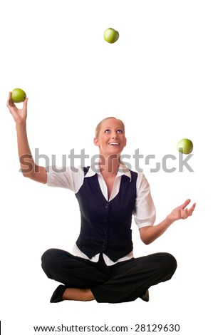 A blond and young woman is sitting on the floor and juggling a green apple